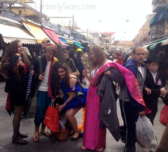 Israeli youth sport their none-too-conservative Purim costumes while a man and an Orthodox boy hurry past on a street in Mahane Yehuda.